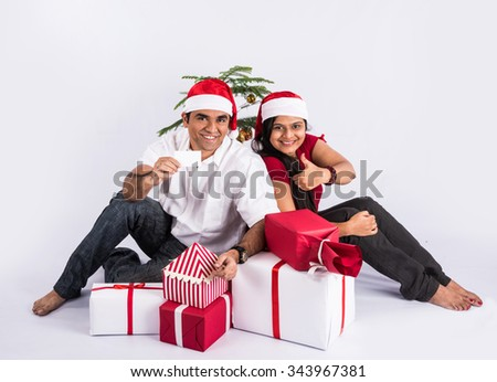 young indian couple sitting with with christmas gifts showing card, asian couple and christmas gift, with santa hat, white background, india and christmas celebration, christmas gift and indian couple