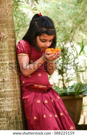 young Indian girl / child / kids wearing traditional dress for Onam, Vishu Kerala India . Asian child. Beautiful daughter traditional India sari. Sweet, happy, smiling child in park smelling flowers  - stock photo
