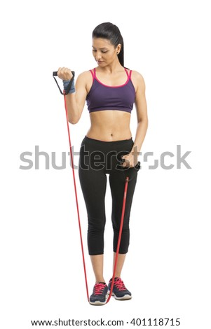 Young Indian girl doing exercise with rubber resistance band. isolated on white. - stock photo