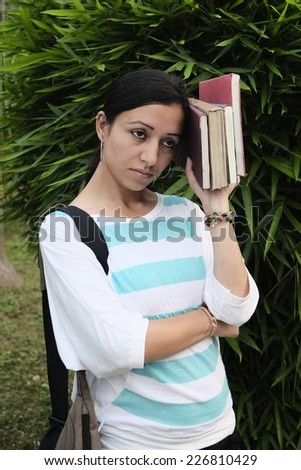 Young indian girl feeling tired  with book in her hand. she is anxious about result or future - stock photo