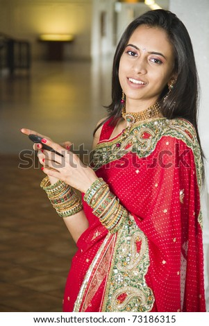 Young Indian girl in traditional clothing using a cellphone. - stock photo