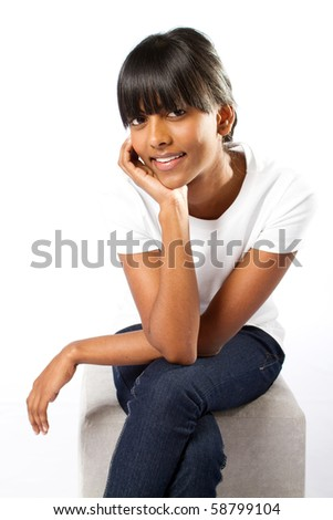 young indian girl sitting on chair - stock photo
