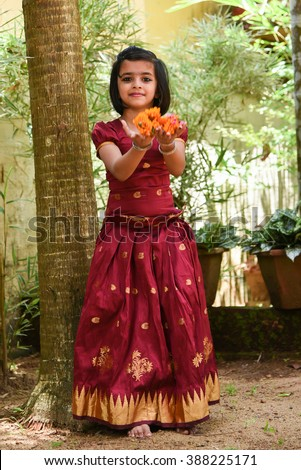 young Indian girl wearing traditional dress for Onam, Vishu Kerala India . Asian child. Beautiful daughter traditional Indian sari. Sweet, happy, smiling child in park playing with flowers, laughing  - stock photo