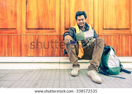 Young indian guy looking city map holding mobile phone - Asian model male next to old wooden door - Cheerful afro american student reading - Concept of tourism DIY and freedom - Soft vintage filter - stock photo
