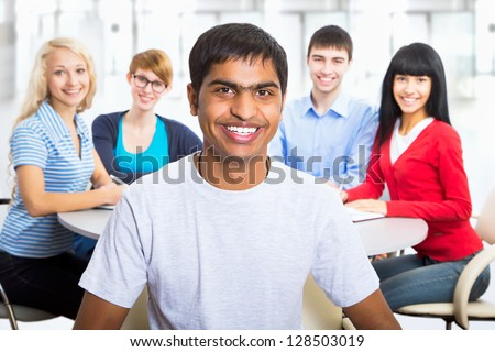 Young indian student and his diversity friends on background - stock photo