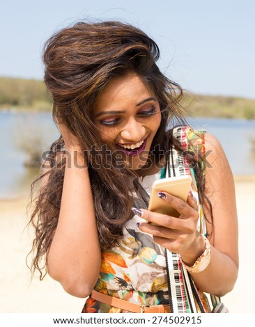 young indian woman checking her text messages - stock photo