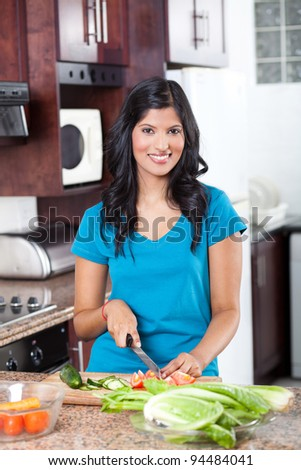 young indian woman cooking in kitchen - stock photo