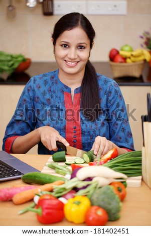 Young Indian woman cutting vegetables in kitchen room - stock photo
