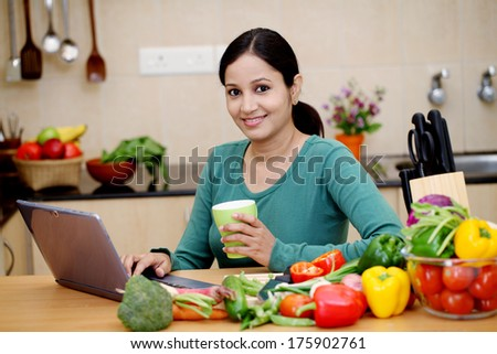 Young Indian woman drinking coffee in her kitchen