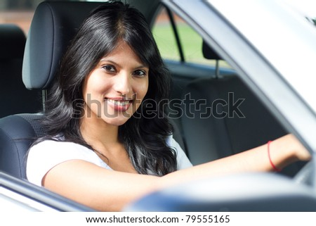 young indian woman driving a car - stock photo