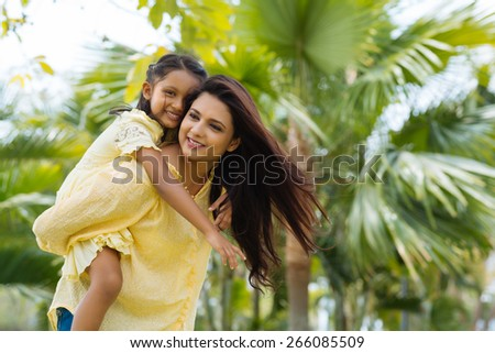 Young Indian woman giving piggyback ride to her daughter - stock photo