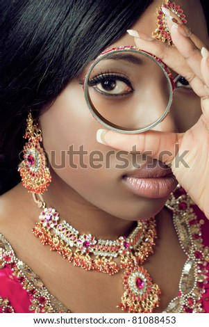 Young indian woman in traditional clothes with golden bridal jewelry, close-up shot - stock photo
