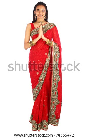Young Indian woman in traditional clothing greeting namaste - stock photo