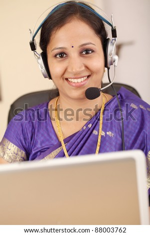 Young Indian woman in traditional Indian dress with headset - stock photo