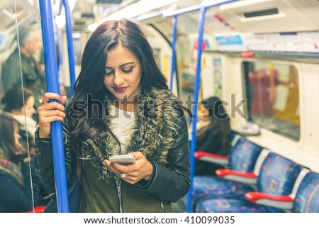 Young indian woman looking at her smart phone and typing while travelling on the tube in London. She is standing and holding with an hand. Transport and commuting concepts. Colours filter added. - stock photo