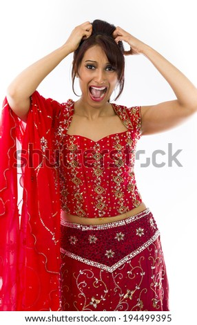 Young Indian woman pulling her hair and screaming in frustration - stock photo