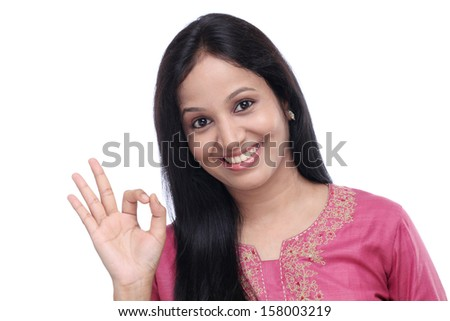 Young Indian woman showing OK sign against white background - stock photo
