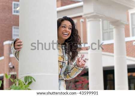 Young Indian woman smiling and waving so someone in the distance. - stock photo