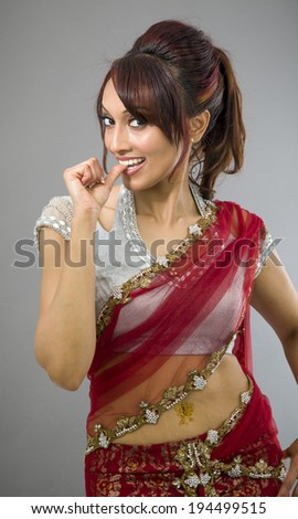 Young Indian woman smiling with finger in mouth - stock photo