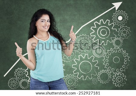 Young indian woman with casual clothes and curly hair showing thumbs up in front of business gear background - stock photo