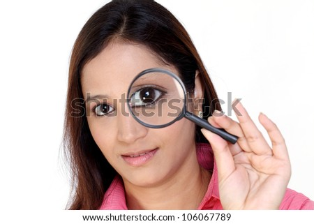 Young Indian woman with magnifying glass at her eye