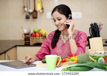 Young Indian woman working with tablet and talking on cellphone - stock photo