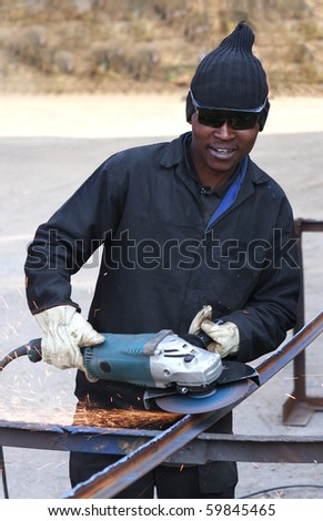 Young industrial worker grinding steel with electric grinder - stock photo