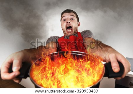 young inexperienced home cook with apron holding pot burning in flames with stress and panic face expression in fire in the kitchen and cooking wrong concept - stock photo