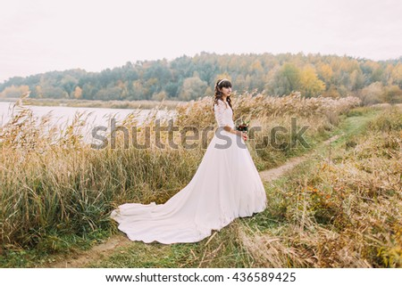 Young innocent bride posing outdoors. Cute charming girl with forest hills on background - stock photo