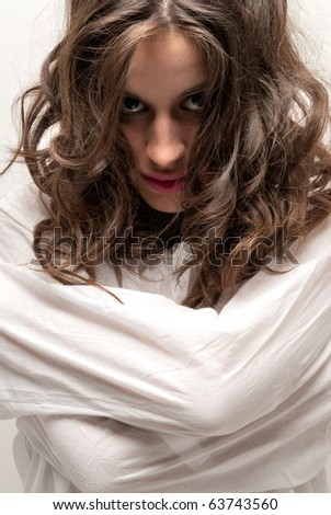 Young insane woman with straitjacket looking at camera close-up portrait - stock photo