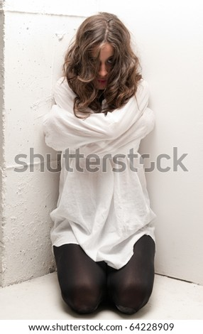 Young insane woman with straitjacket on knees looking at camera - stock photo