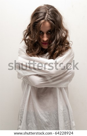 Young insane woman with straitjacket standing looking at camera - stock photo