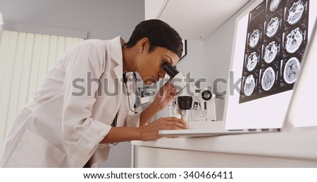 Young intelligent  female doctor looking in a microscope - stock photo