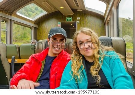 Young inter ethnic couple traveling in panoramic train to Machu Picchu - stock photo