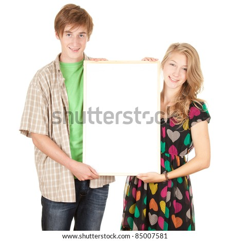 young interested couple holding blank billboard, poster, white background - stock photo