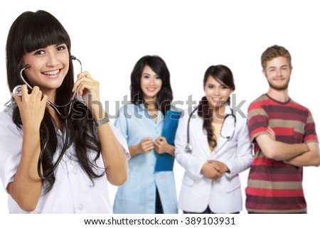 young intern medical doctor smiling to the camera. friend at the background - stock photo