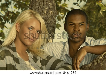 young interracial couple next to a tree - stock photo