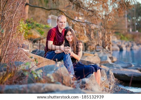 Young interracial couple relaxing together on rocky shoreline by lake - stock photo