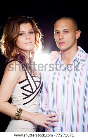 Young interracial cute looking couple over black background.