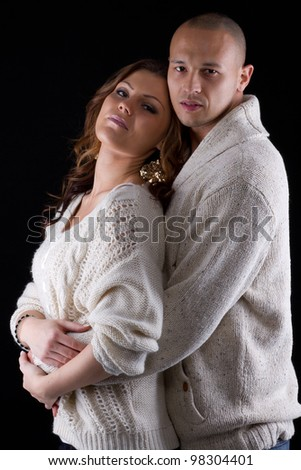Young interracial cute looking couple over black background. - stock photo