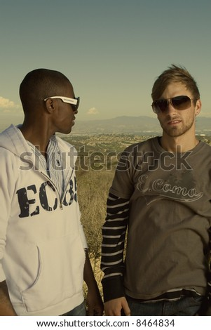 young interracial men standing in a desert field - stock photo