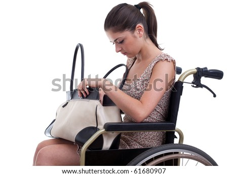young invalid woman with bag on the wheelchair, isolated - stock photo
