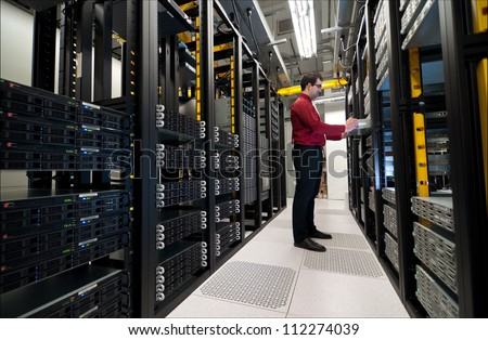 Young IT administrator installing a new rack mount server. Large scale storage server is also seen. - stock photo