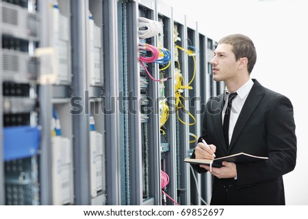 young it  engeneer business man with thin modern aluminium laptop in network server room - stock photo
