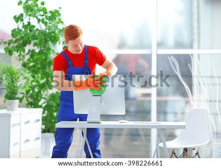 Young janitor cleaning computer monitor in office