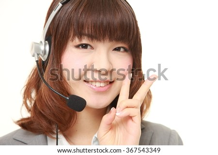 young Japanese Business woman  of call center showing a victory sign - stock photo