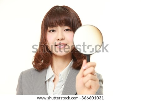 young Japanese businesswoman with a magnifying glass  - stock photo