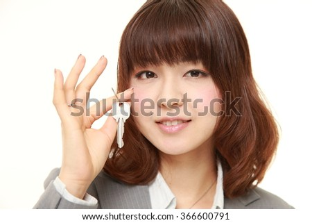 young Japanese businesswoman with home key - stock photo