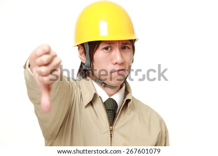 young Japanese construction worker with thumbs down gesture