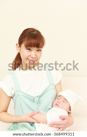 young Japanese mom and her sleeping baby - stock photo